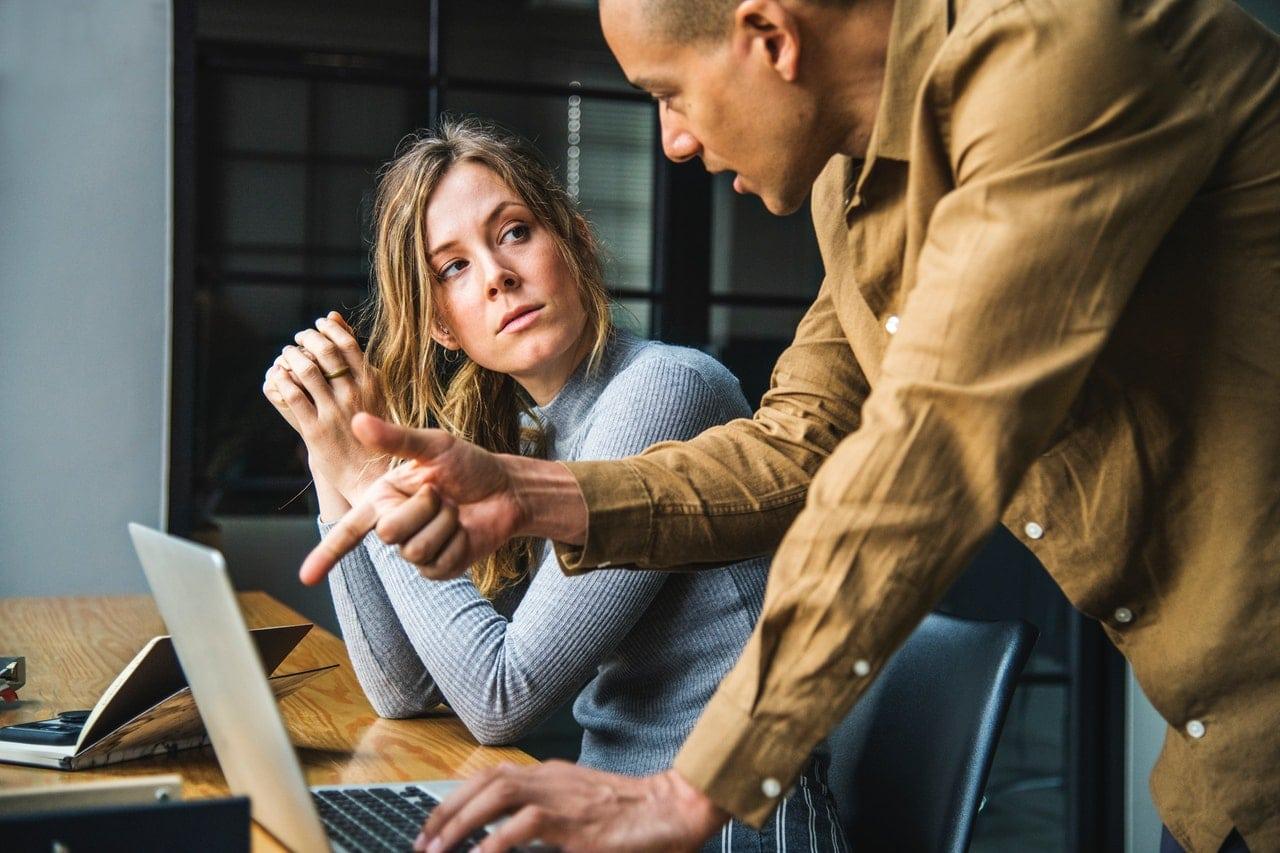 Homem e mulher conversando em frente a notebook