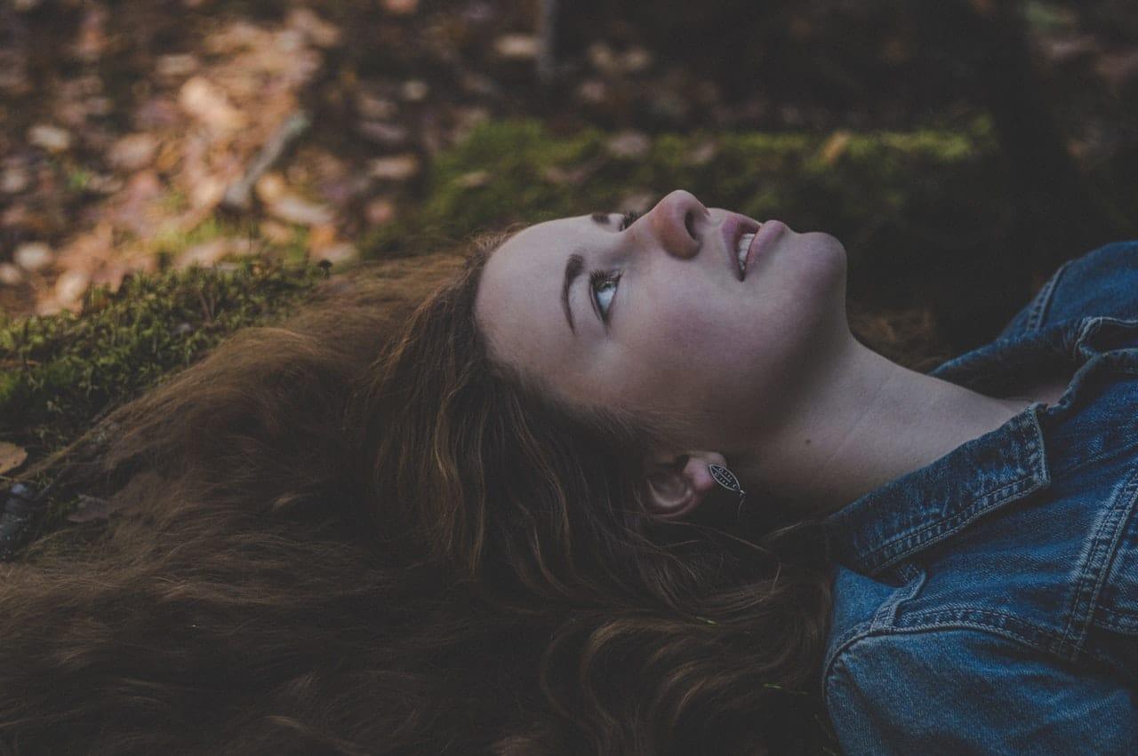 Garota deitada em gramado com cabelos para cima olhando para o céu