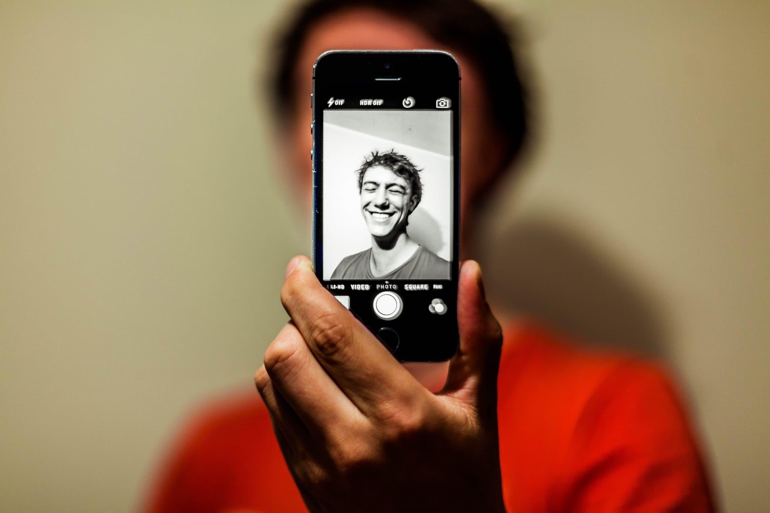 Homem em foto de celular em foco com corpo ao fundo