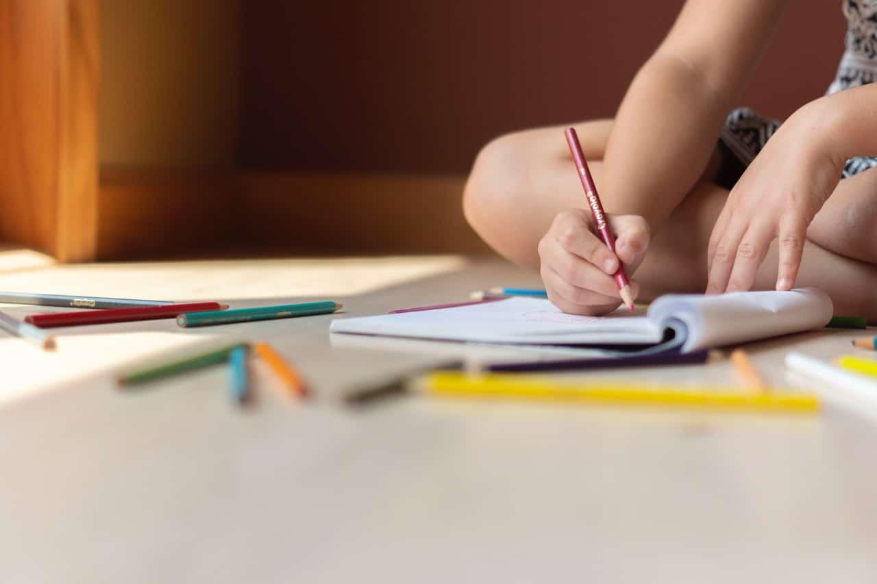 Mão de criança escrevendo