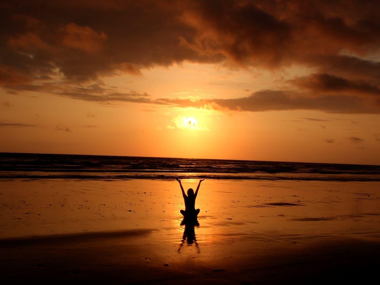 Mulher em praia com sol ao entardecer ao fundo