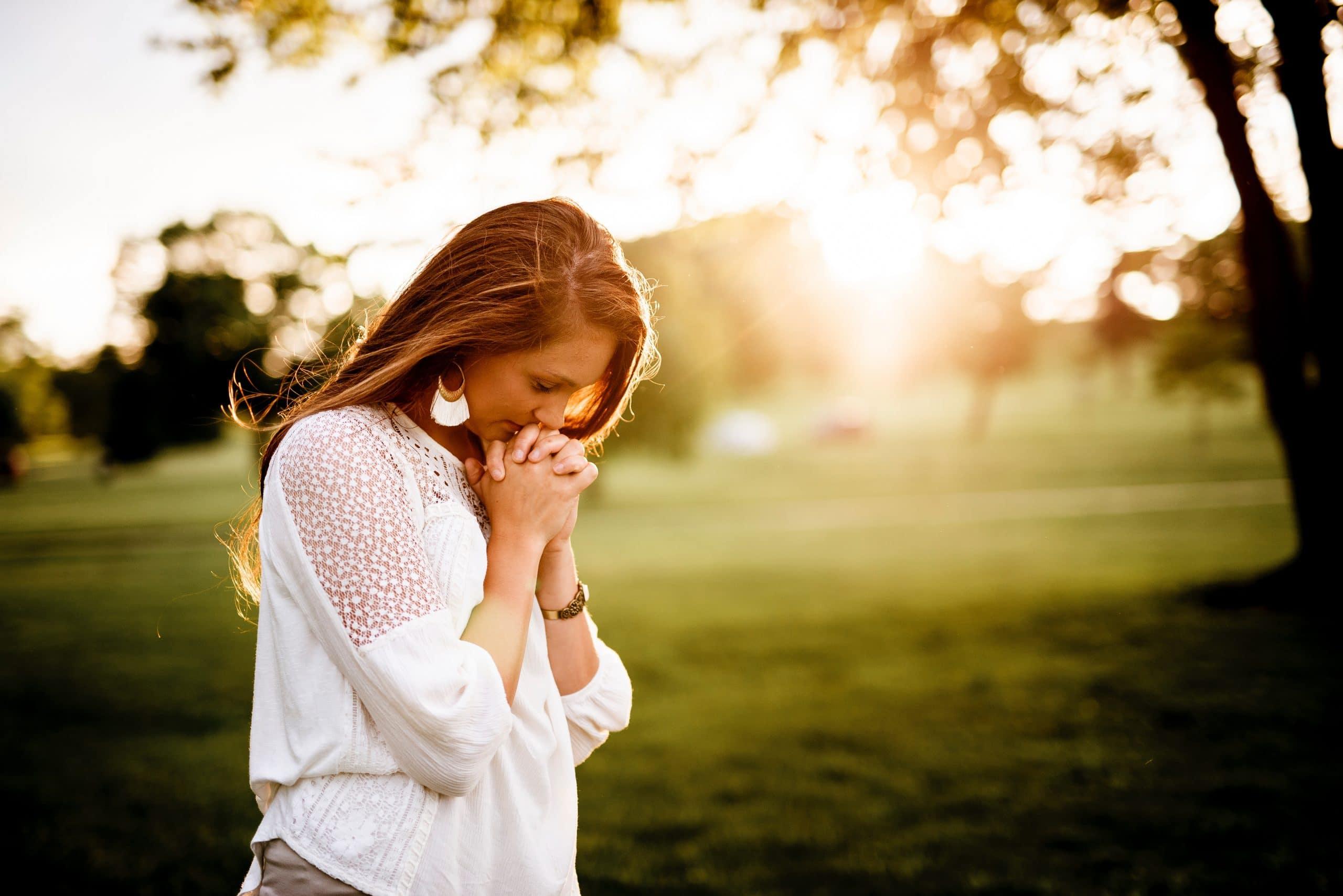 Mulher com a cabeça baixa e as mãos em oração no meio de um parque ensolarado.