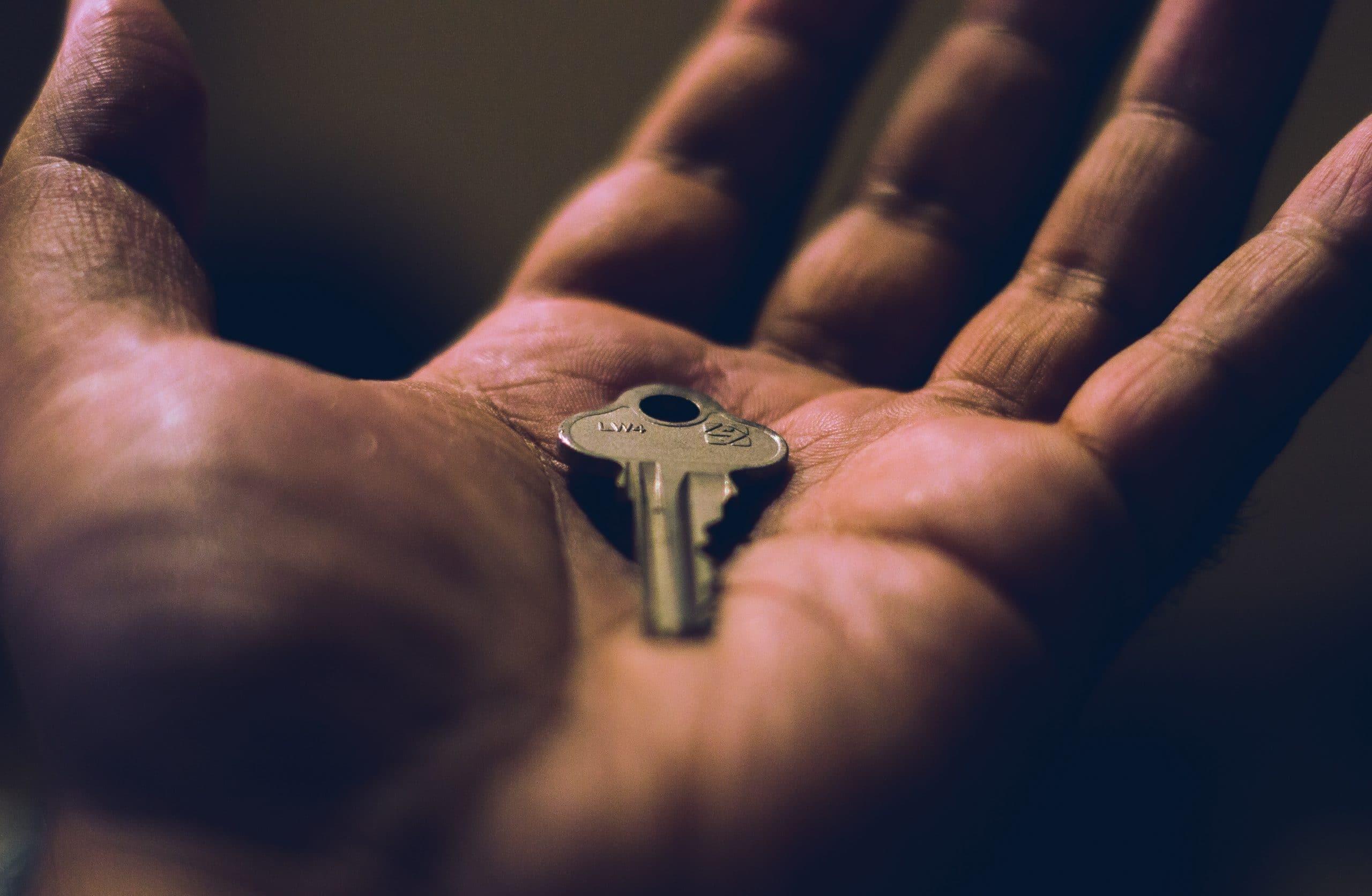 Mão aberta com uma chave na palma.