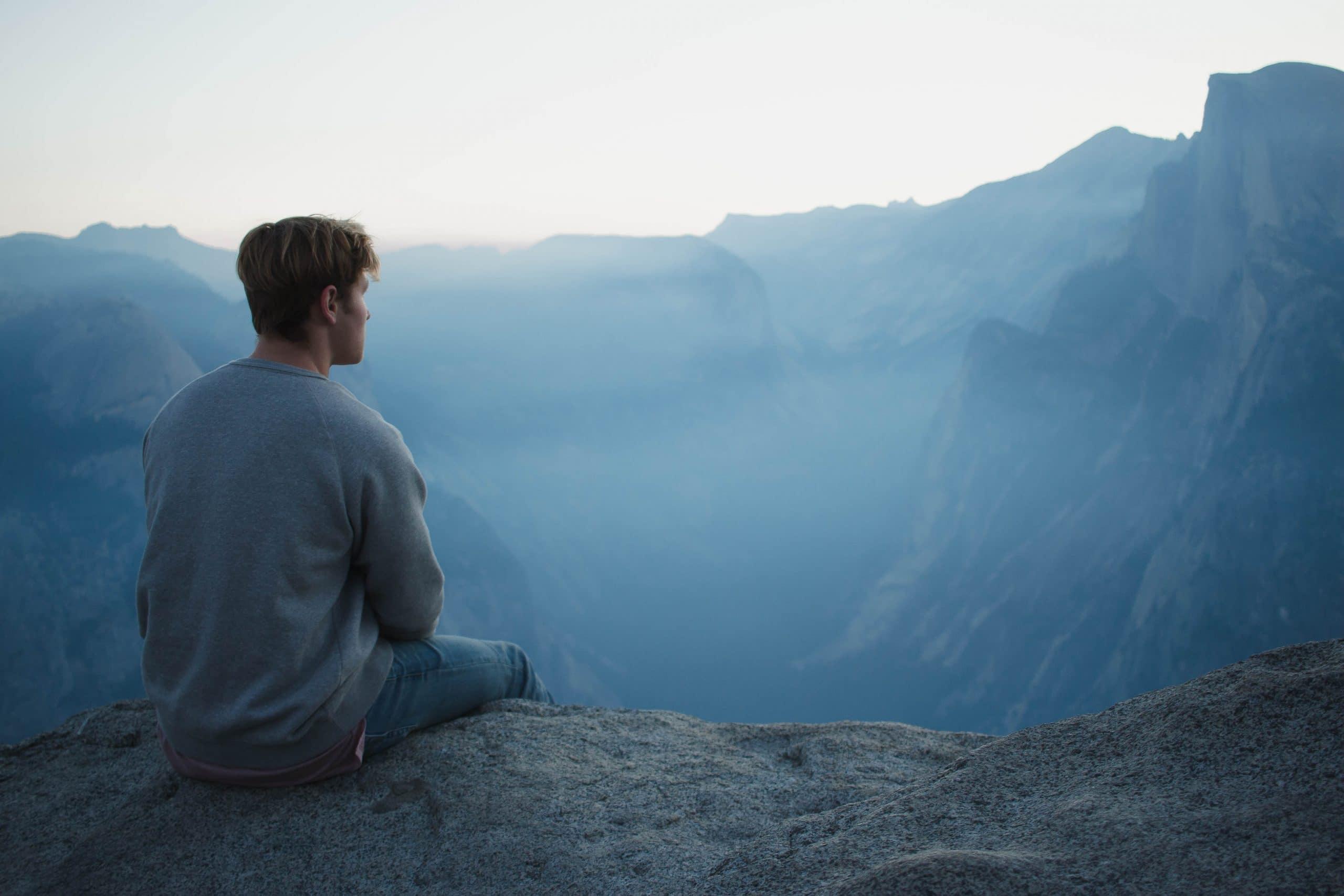 Homem sentado no topo de uma montanha, observando o horizonte.