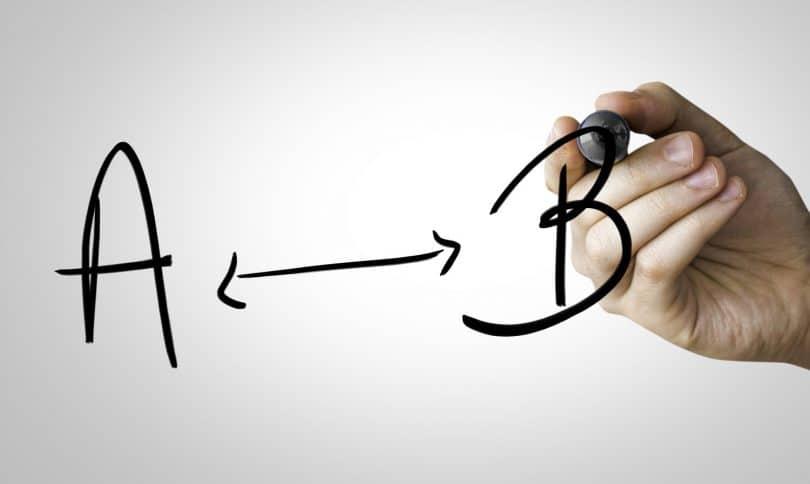 Mão escrevendo de caneta uma seta entre A e B.