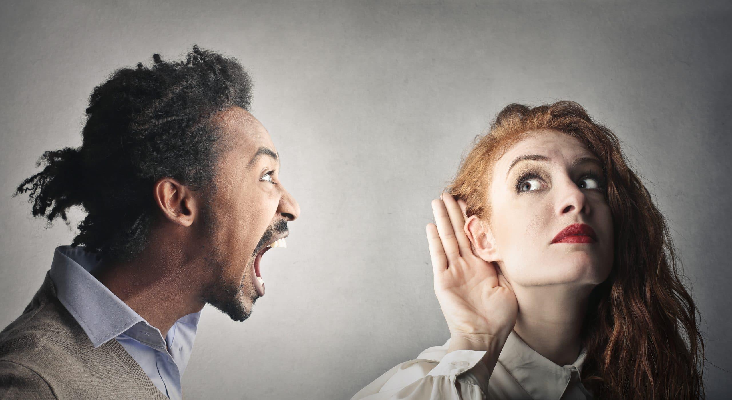Homem gritando para mulher com mão no ouvido.