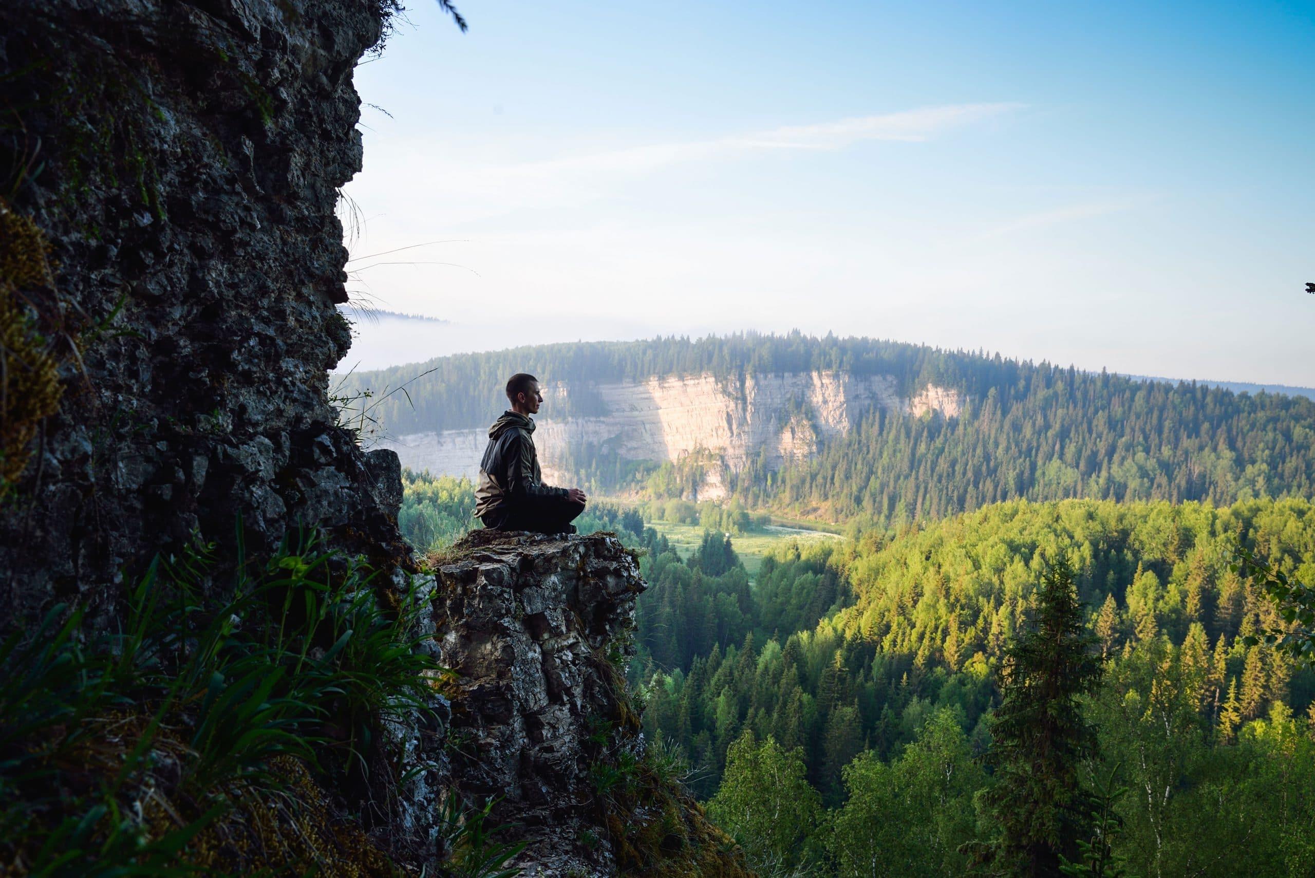 Homem sentado meditando.