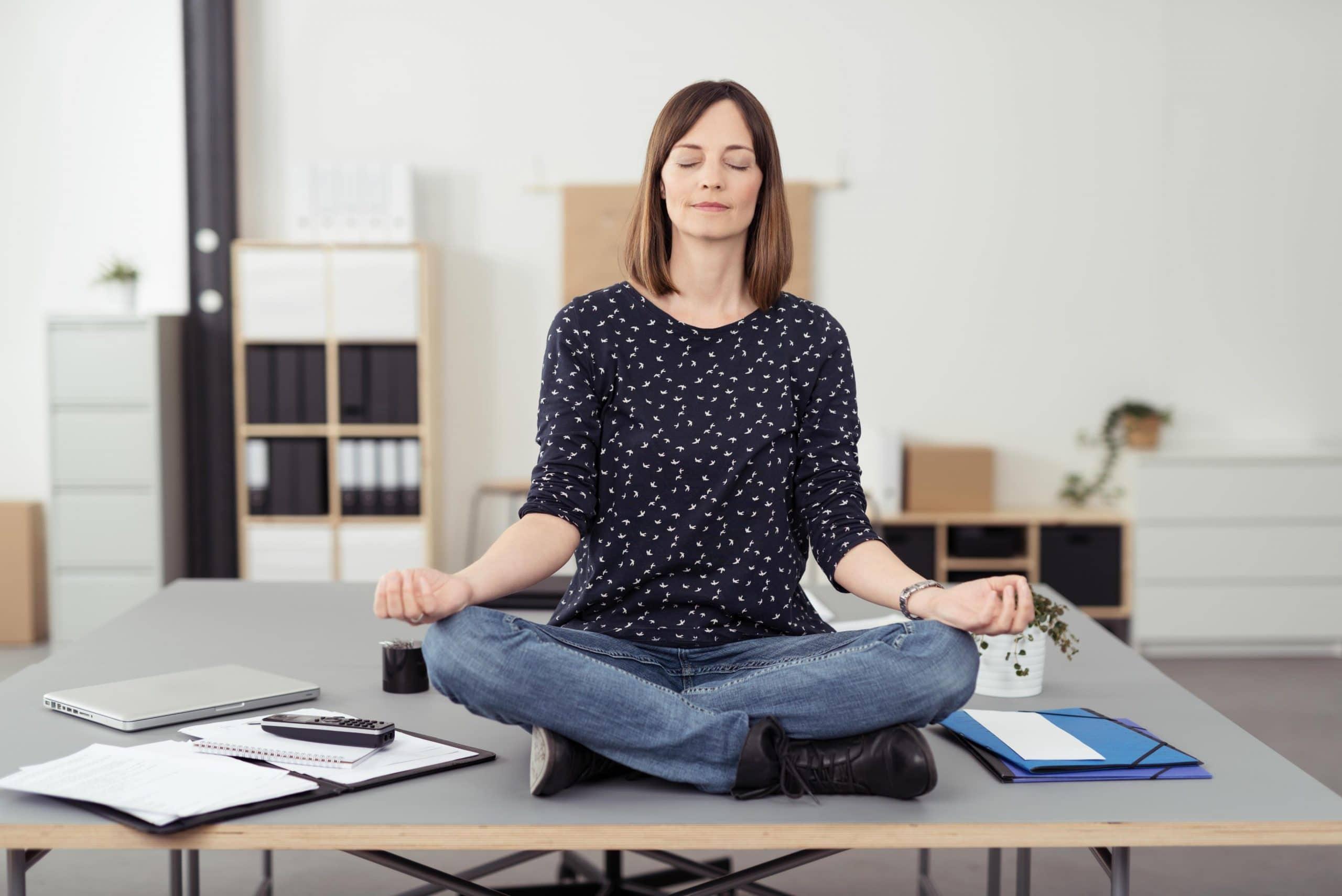 Mulher praticando yoga no escritório em cima da mesa.