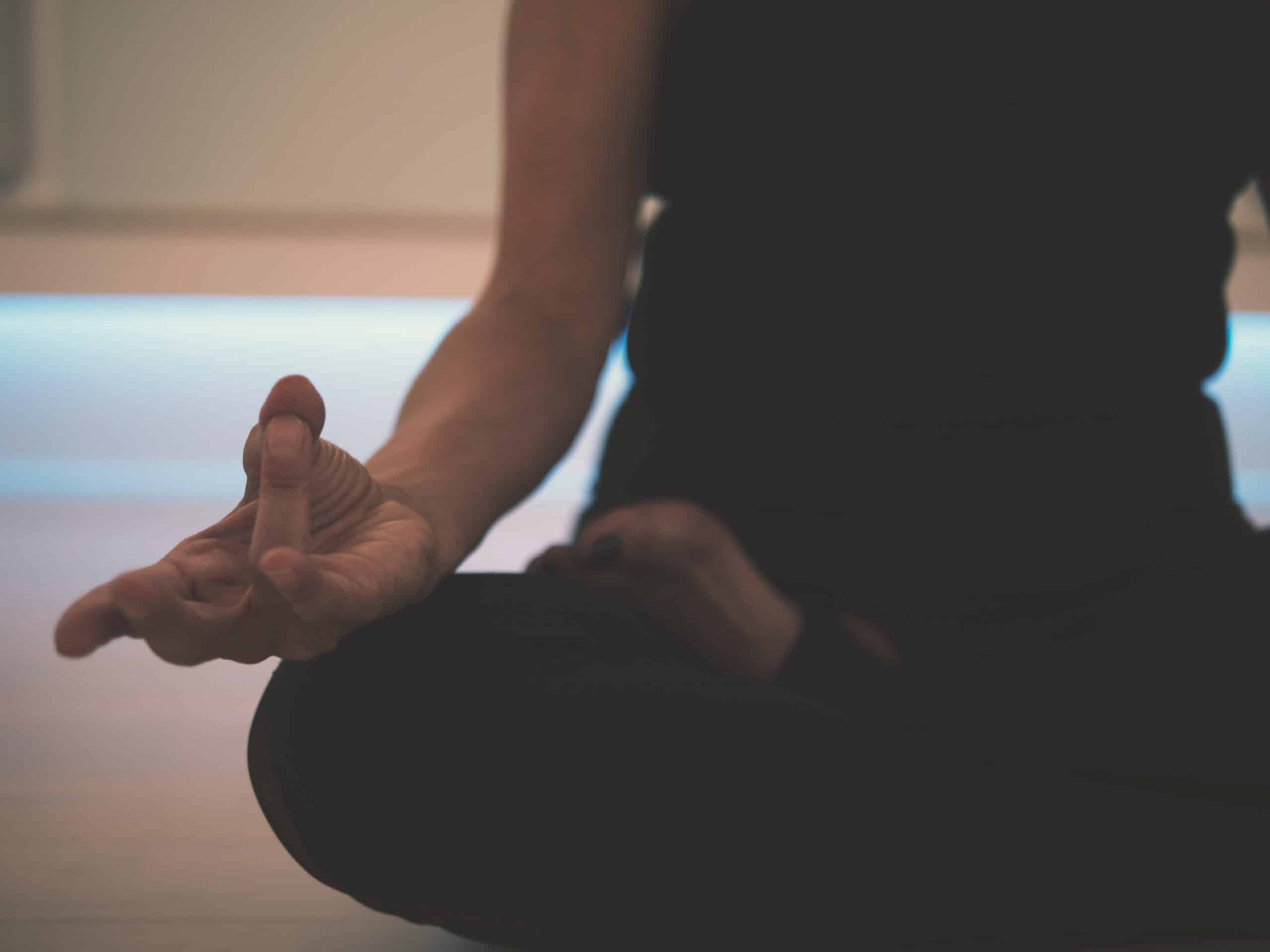 Mão de mulher em posição de meditação apoiada em perna cruzada