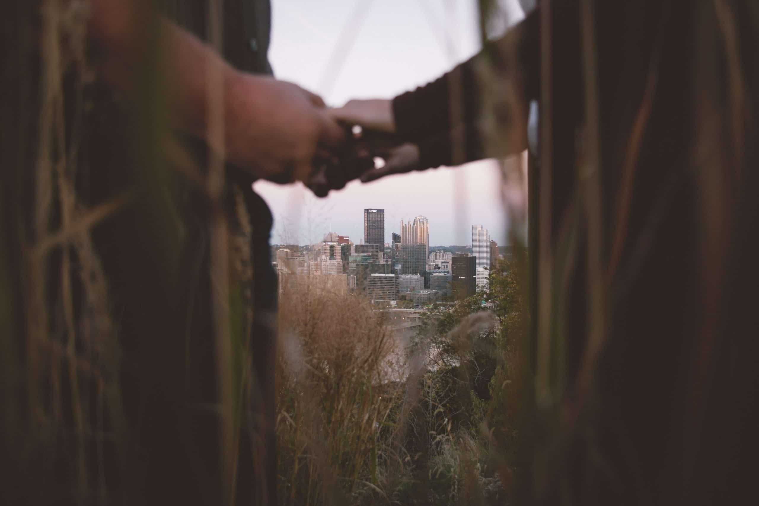 Duas pessoas dando as mãos em frente a uma cidade.