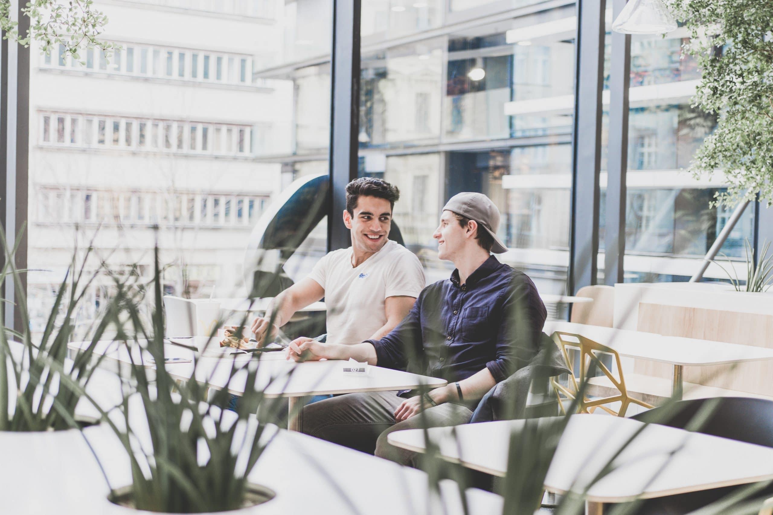 Casal conversando na mesa em um ambiente arejado com prédios ao fundo.