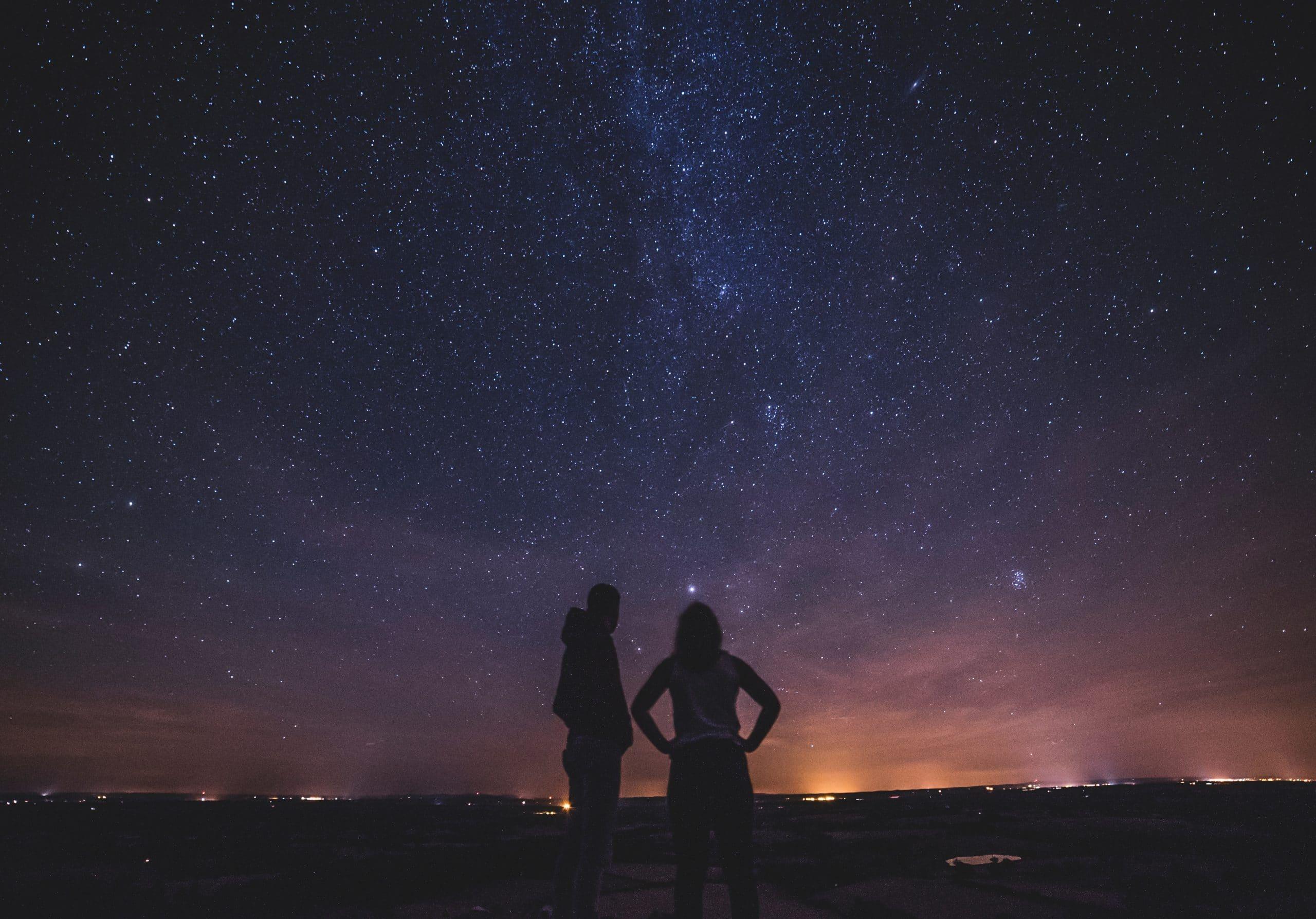 Um homem e uma mulher diante de um céu estrelado.
