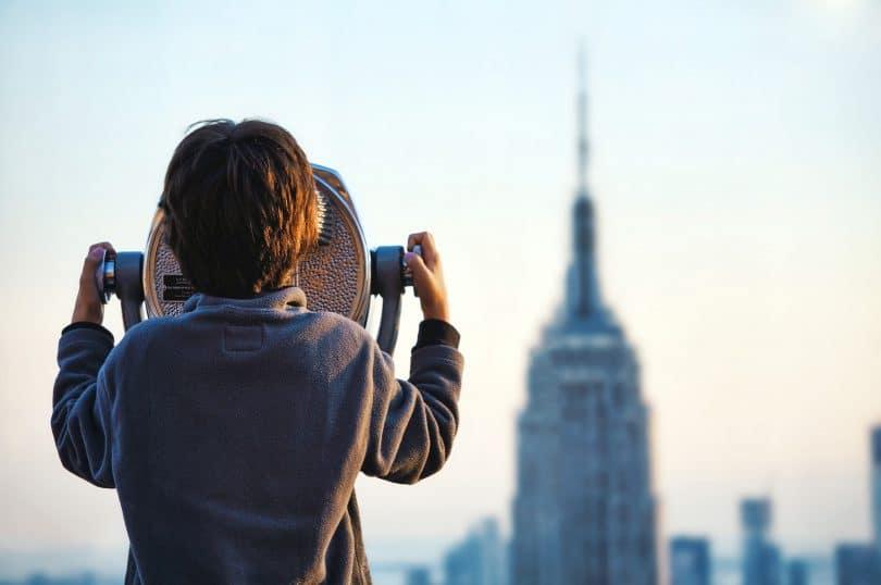Menino de costas olhando para uma torre de fundo.