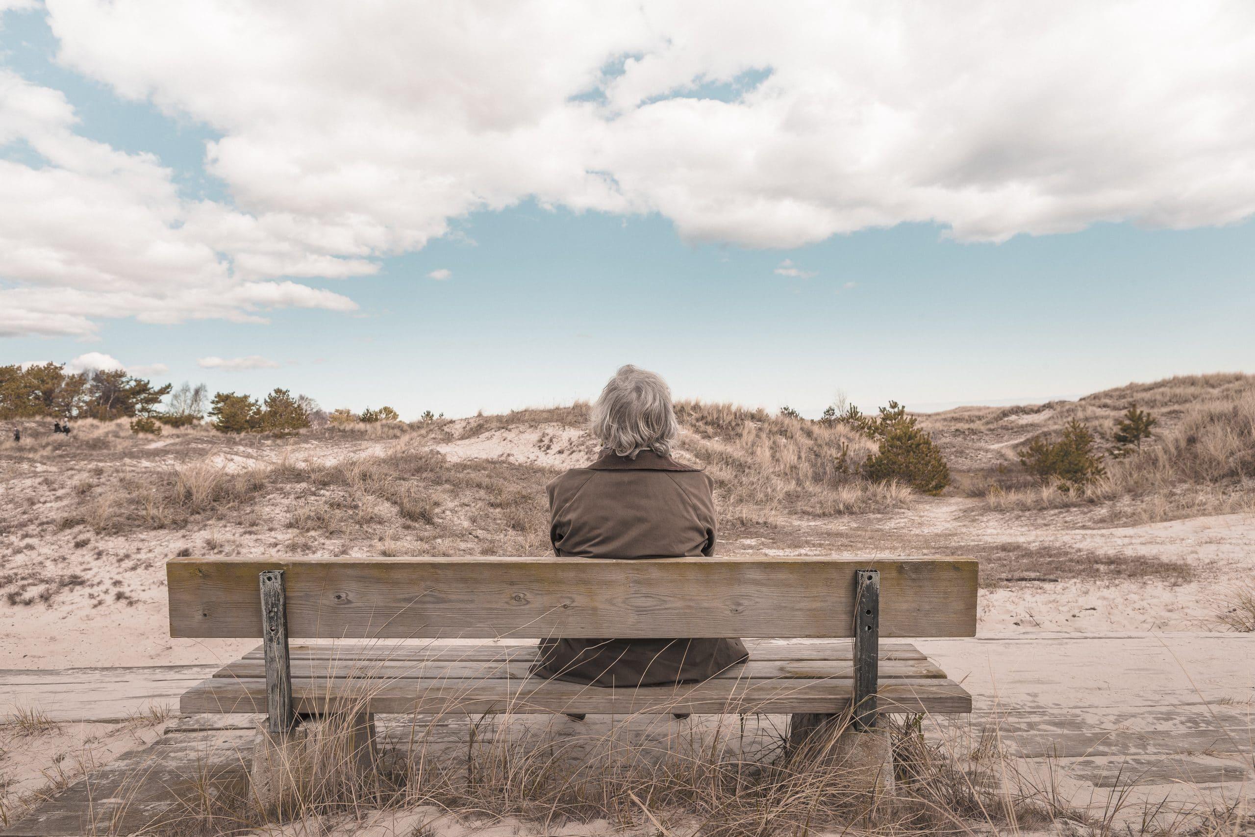 Mulher de costas sentada em um banco observando a paisagem.