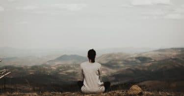 Mulher de costas meditando em uma montanha.