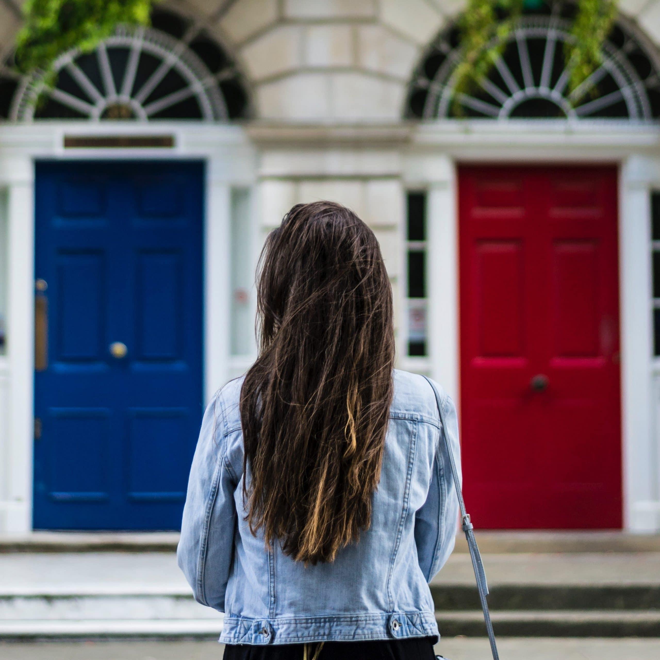 Mulher observando duas portas diferentes.