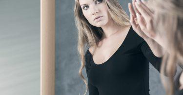 Mulher loira de blusa preta se encarando no espelho.