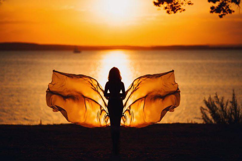 """Mulher com """"asas"""" de borboleta em frente ao mar no pôr-do-sol."""