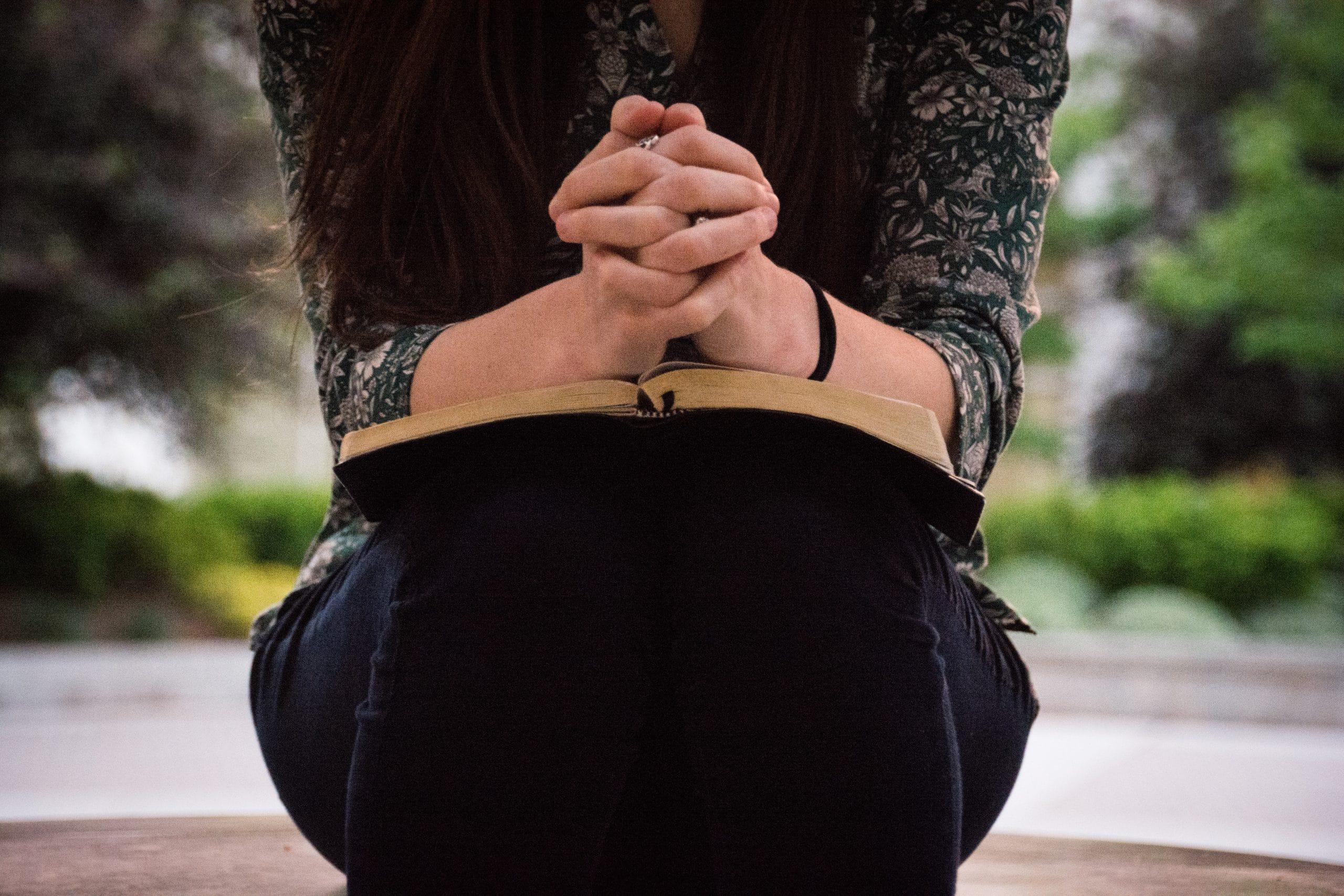 Mãos de mulher sobre bíblia rezando