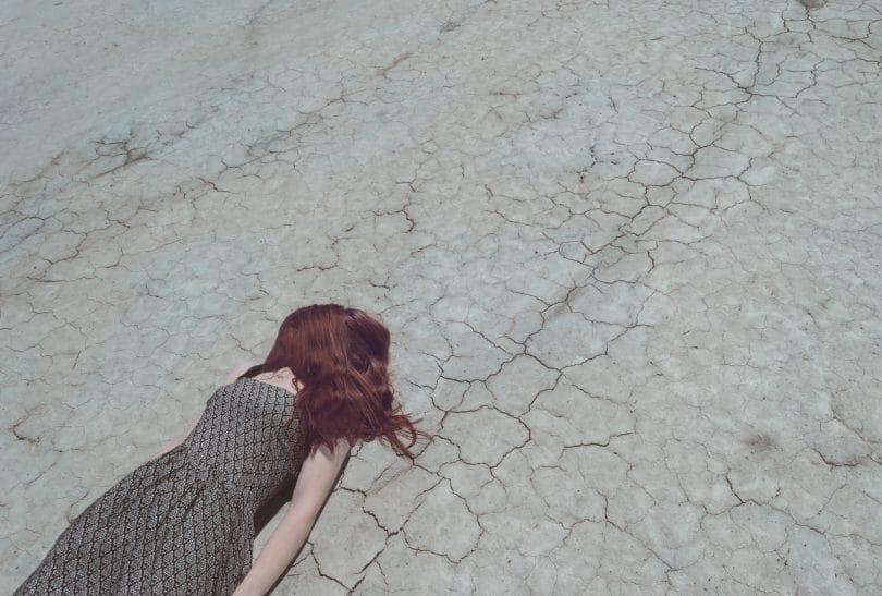 Garota da pele branca e cabelos ruivos vestindo um vestido estampado com detalhes em marrom e branco. Ela está deitada sobre um chão rachado com seus cabelos cobrindo o rosto.