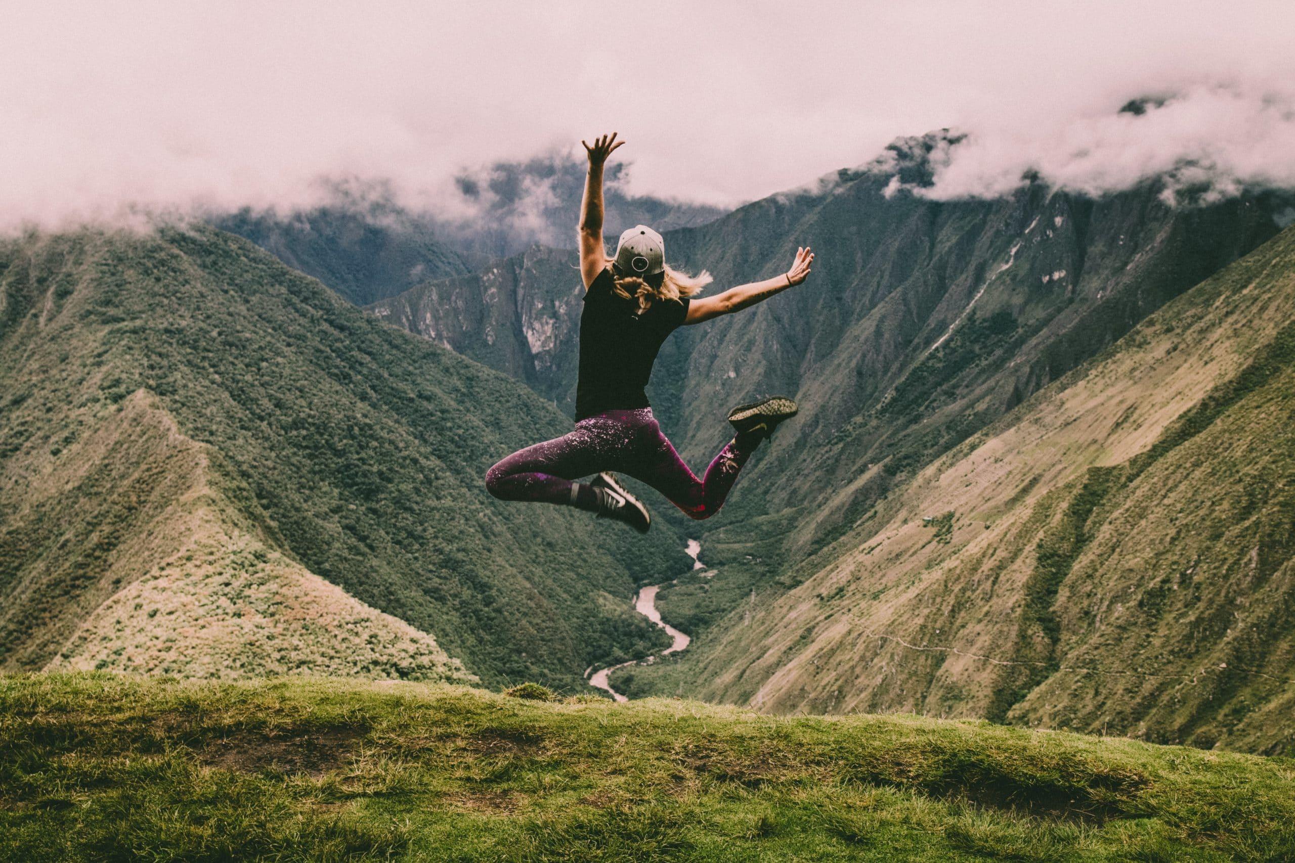 Mulher pulando no alto de montanha com montanha e céu nublado ao fundo