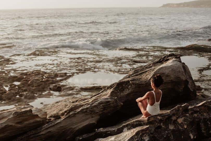 Mulher sentada em uma rocha olhando o mar