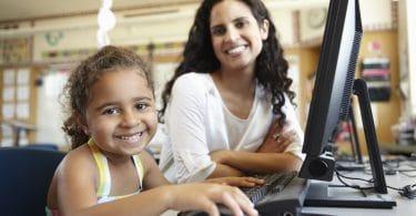 Professora e aluna sorrindo sentadas de frente a um computador.
