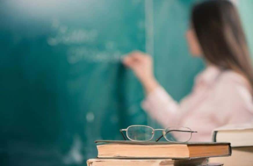 Professora escrevendo na lousa.