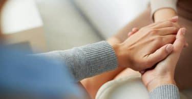 Mãos de terapeuta e paciente unidas em sessão de psicoterapia.