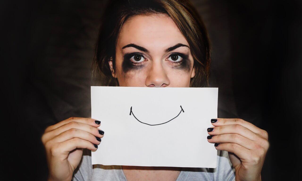 Mulher com um sorriso falso na frente do rosto.