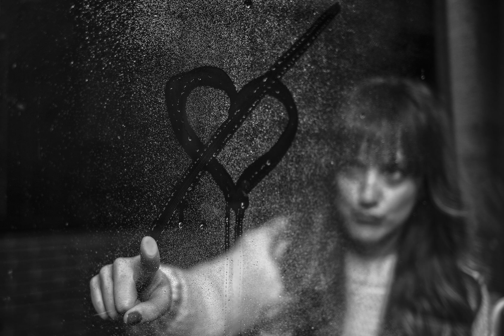 Mulher desenhando um coração riscado no vidro molhado.