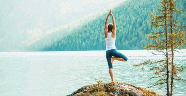 Mulher praticando yoga em frente a um ambiente marcado pela natureza.