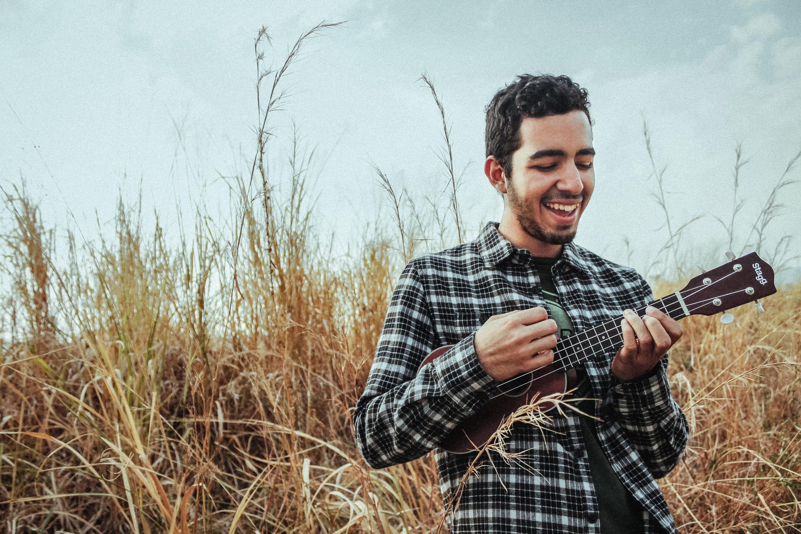 Rapaz tocando Ukulele em campo com matos secos sorrindo