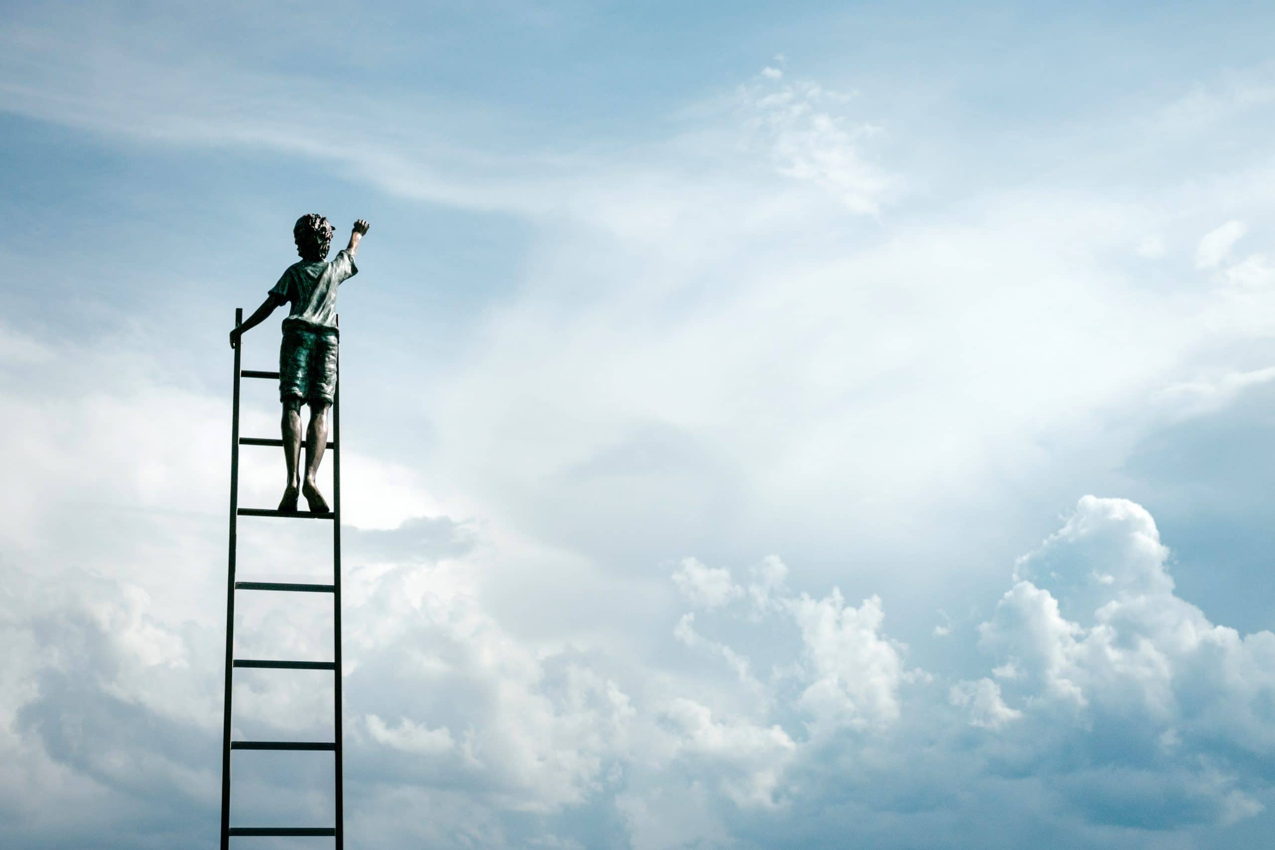 Menino subindo escadas no céu.