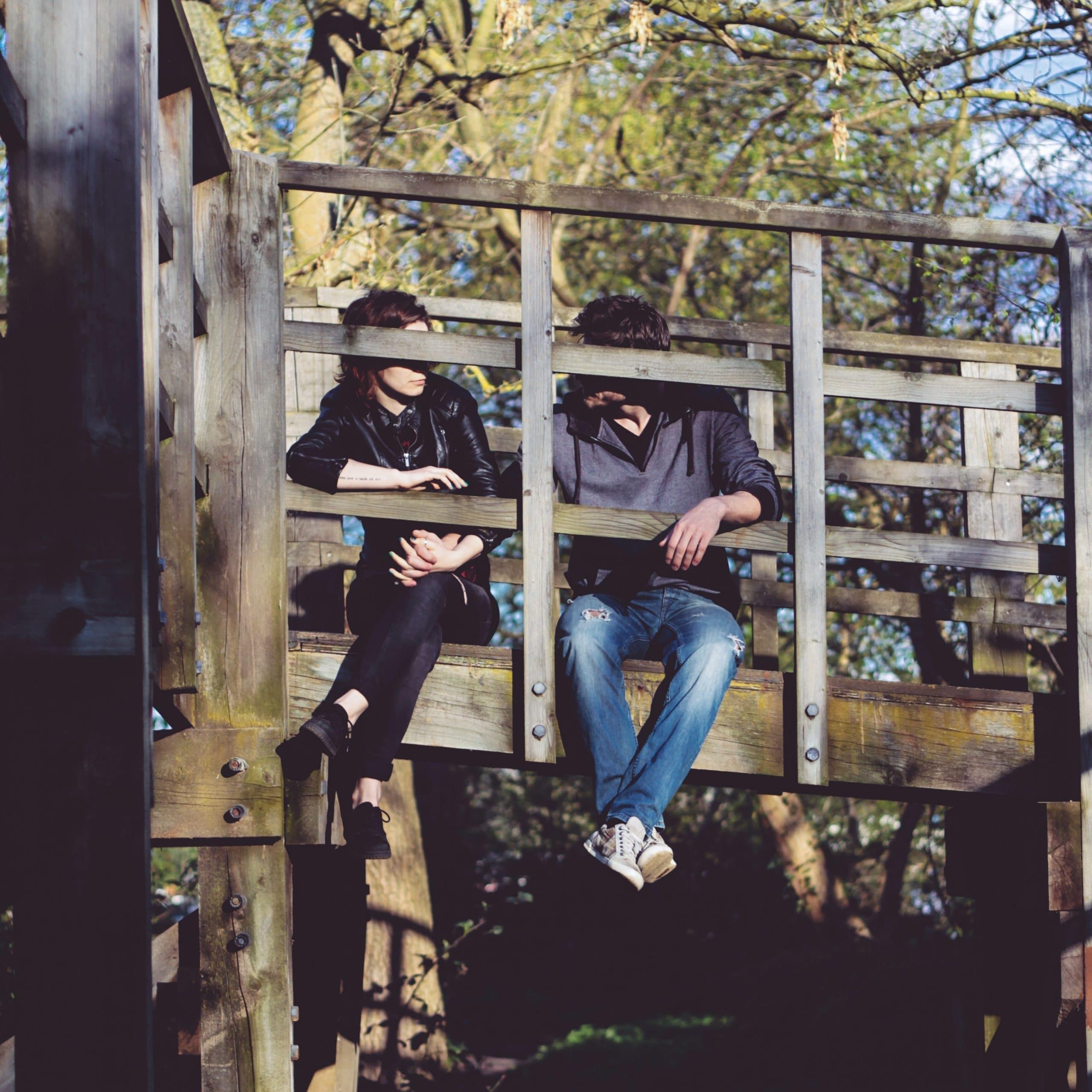 Casal em uma ponte de madeira conversando.