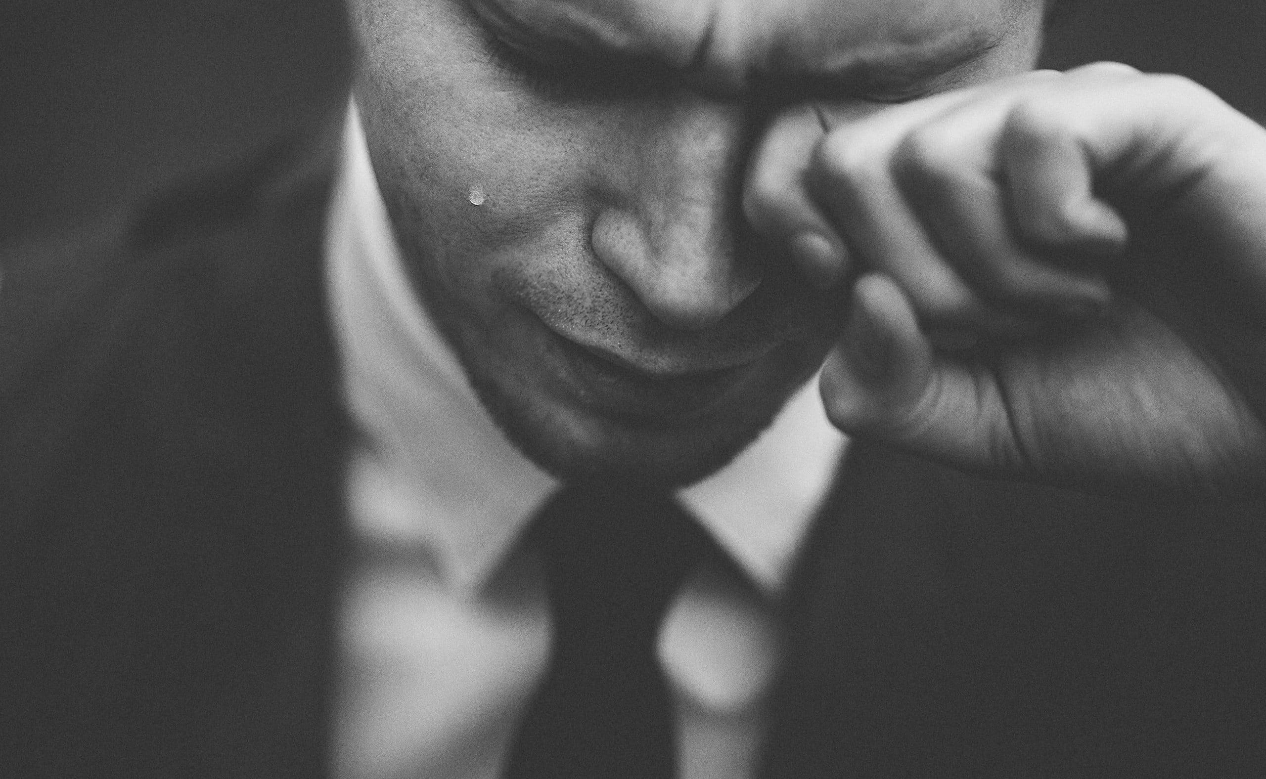 Homem de terno chorando.