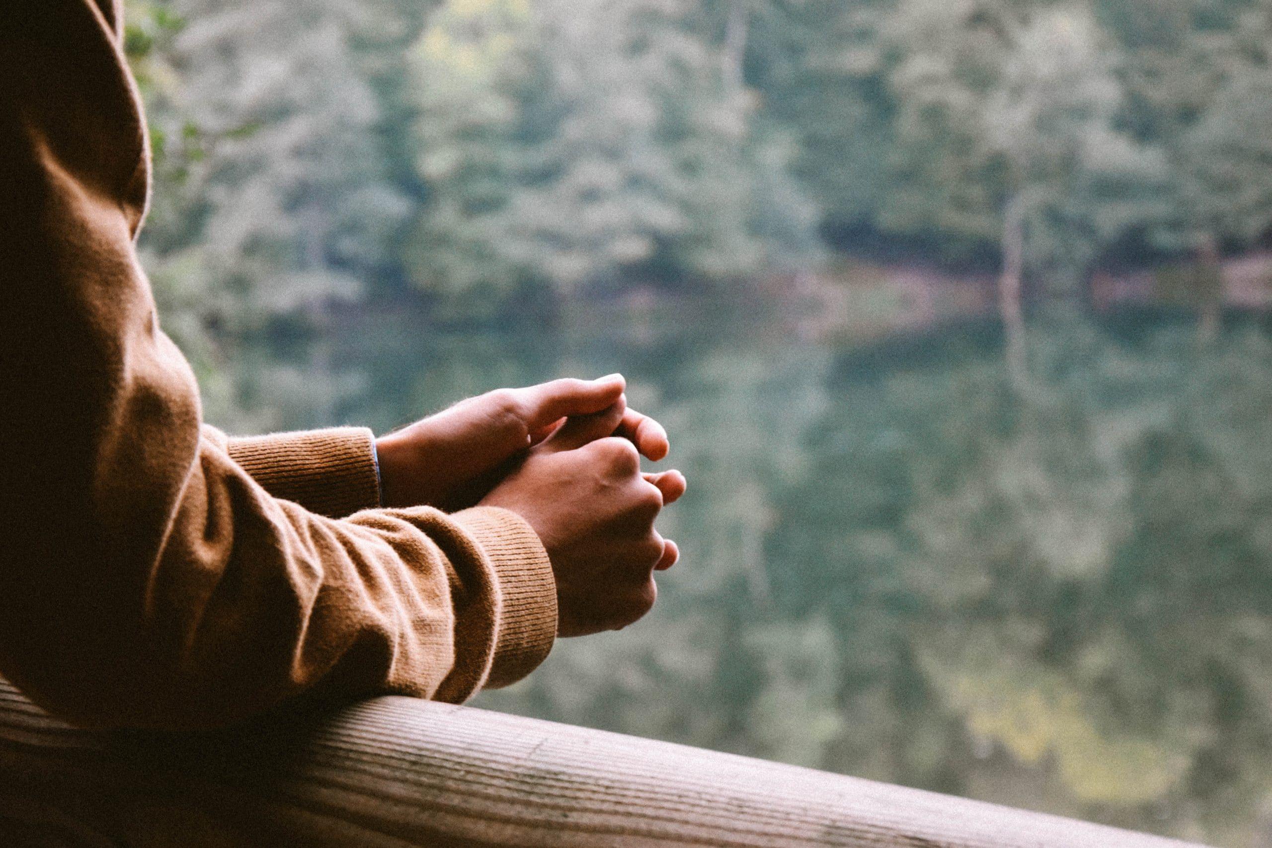 Pessoa com os braços encostados em uma varanda em frente a uma floresta.