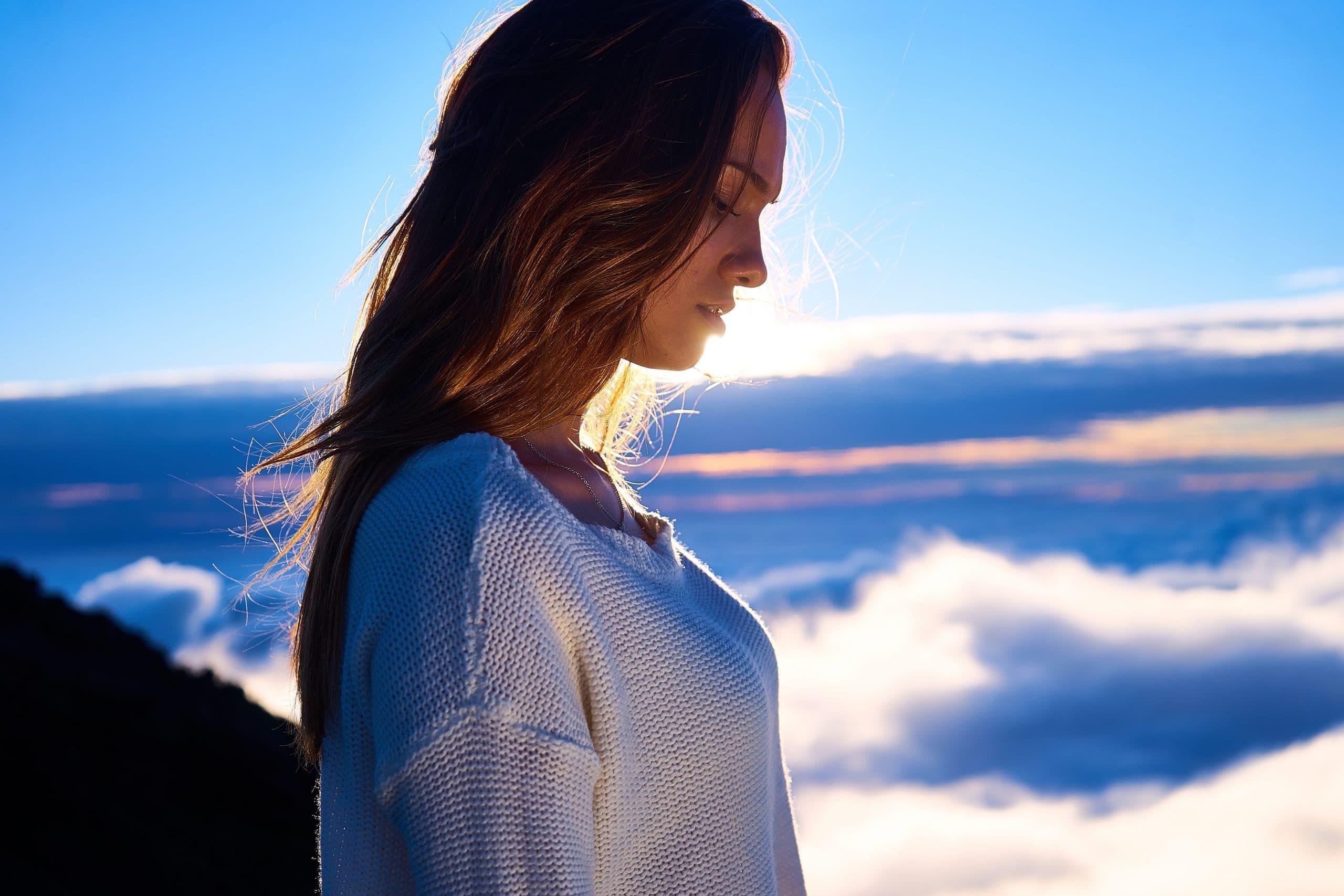 Mulher no alto de montanha com céu de nuvens e sol refletindo ao fundo
