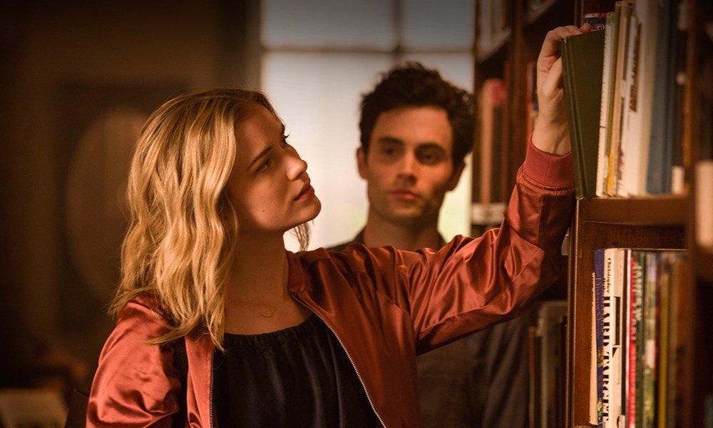 Homem observando mulher em biblioteca.