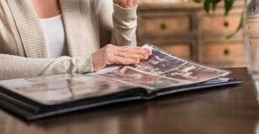 memórias: Senhora de idade sentada em mesa de madeira olhando álbum de fotos.