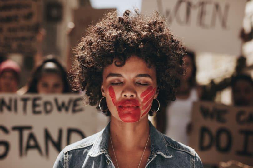 Mulher de olho fechado e mão vermelha pintada na boca.