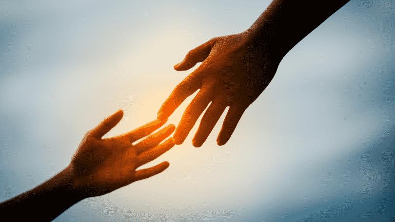 Pessoa estendendo a mão para outra pessoa