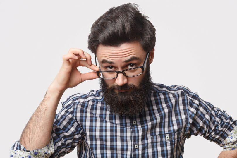 Homem barbudo coma mão em seu óculos.