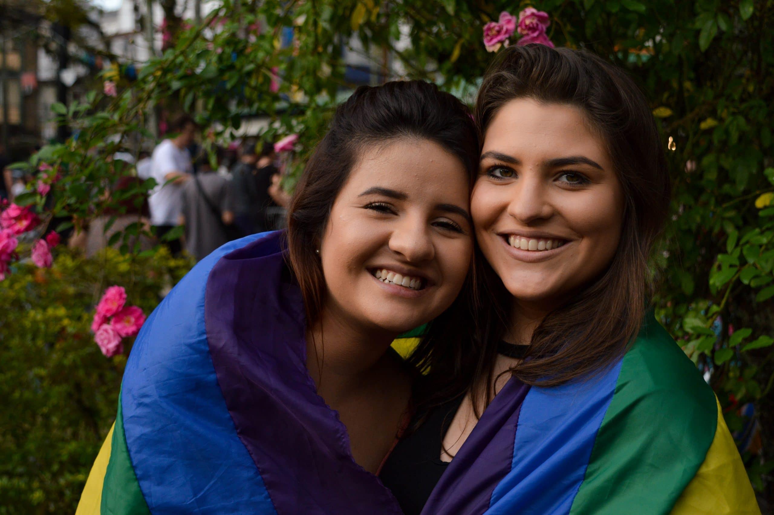 Casal feminino enrolado em bandeira LGBT
