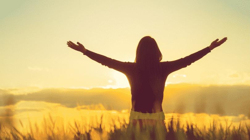 Mulher agradecendo com os braços erguidos para o céu