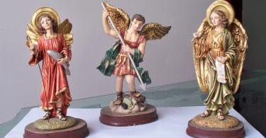 Dia do Arcanjos: Estátuas dos Arcanjos Miguel, Gabriel e Rafael, todas em cima de uma mesa.