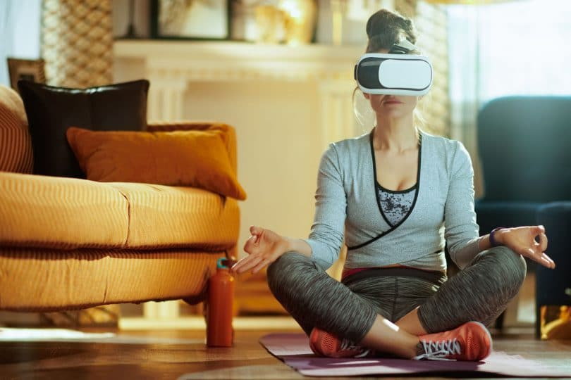Mulher sentada em posição de meditação com óculos de realidade virtual