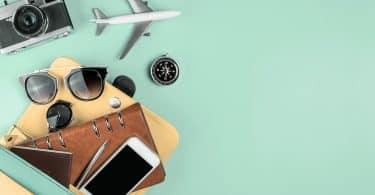 Objetos de viagem e um avião simbólico sobre fundo verde.