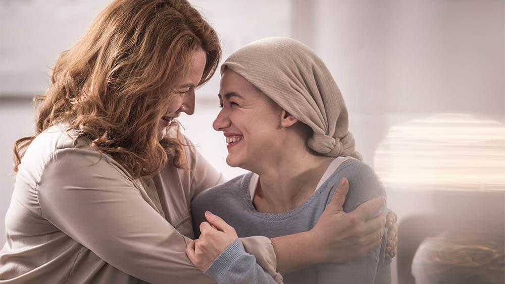 Duas mulheres se abraçando e sorrindo, uma com pano na cabeça.