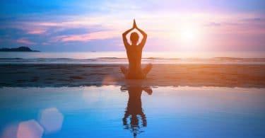 Silhueta de pessoa sentada de pernas cruzadas, praticando yoga, perto de um lago, sob um céu ensolarado.